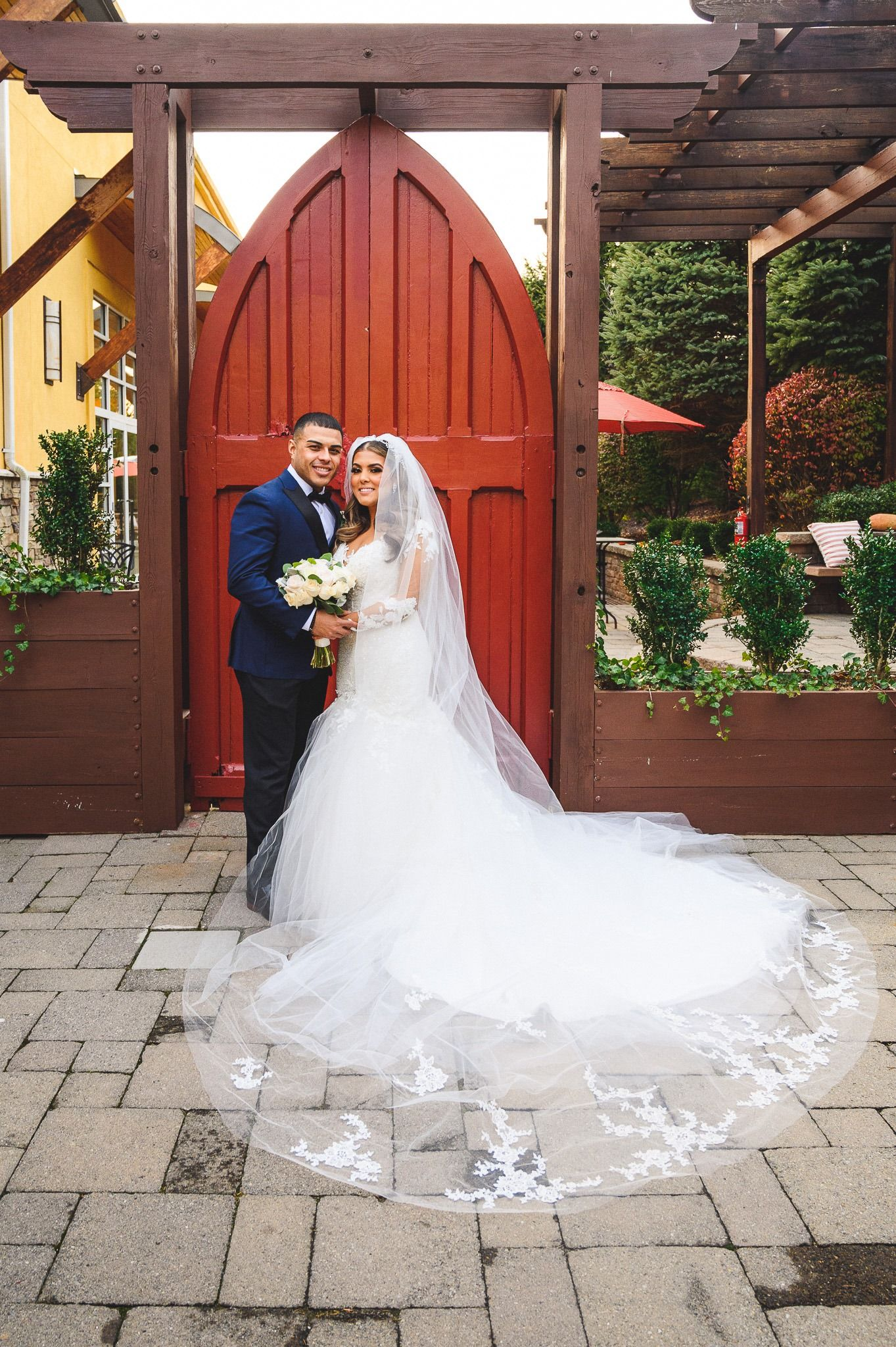 bride and groom portrait in front of red doors at stone house