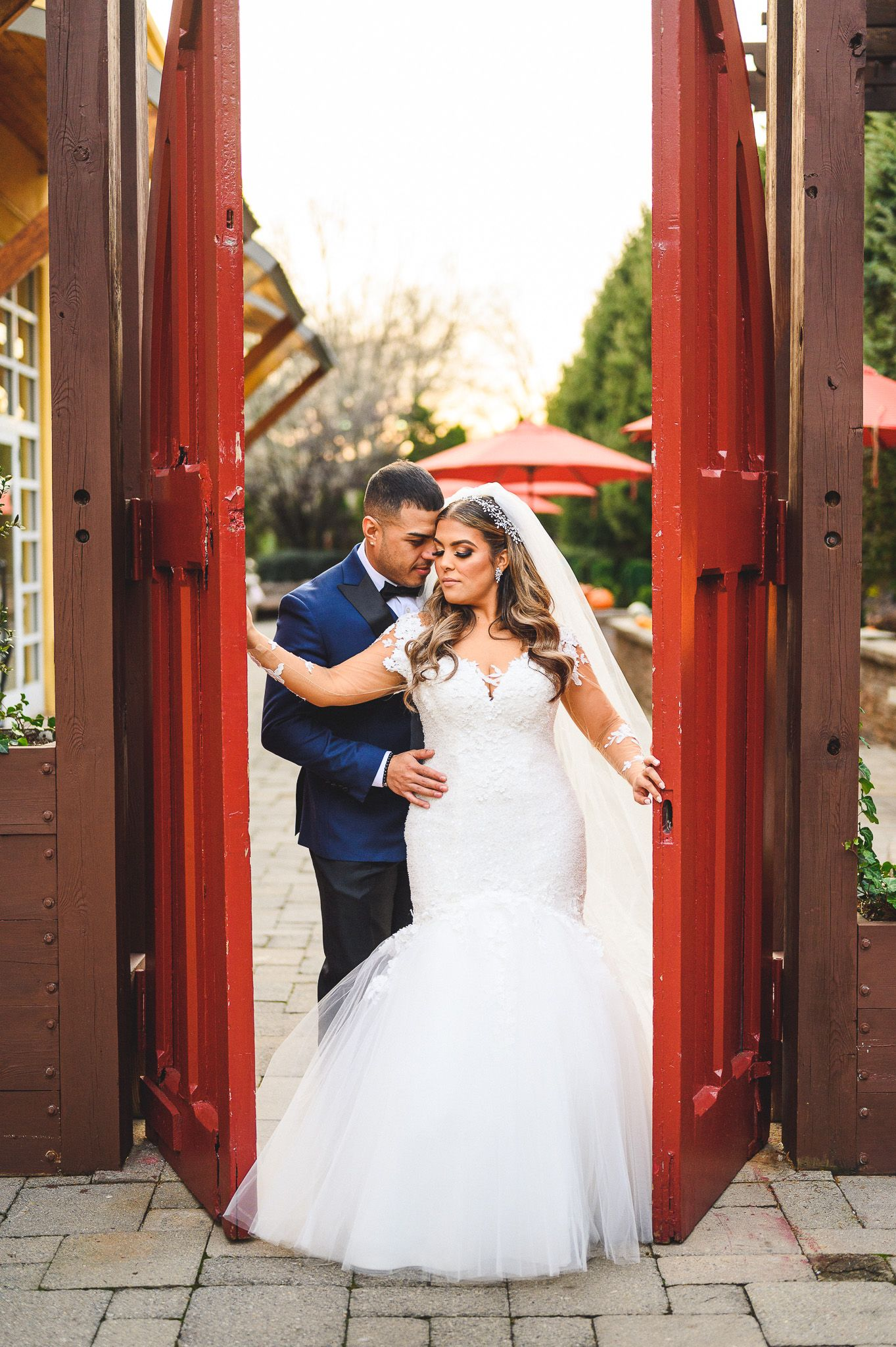 groom holding his bride in between red doors at stone house