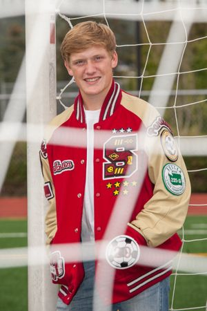 A Highschool boy with his letterman jacket on looking through a soccer goal.