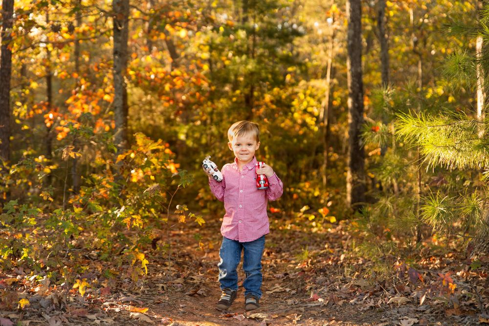 Little boy holding his toy cars in Colonel Francis Beatty park