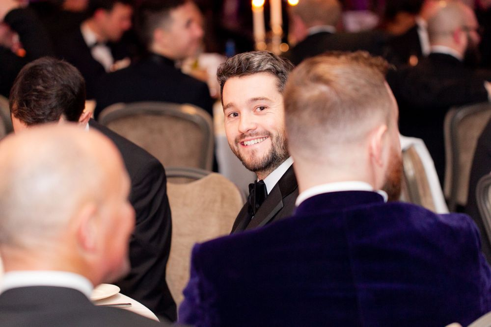 Man in a tuxedo looks directly at the camera through a crowd at a charity gala - Event Photography