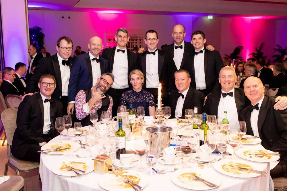 A crowd wearing black tie clothing poses at their table at a charity gala dinner - Event Photography