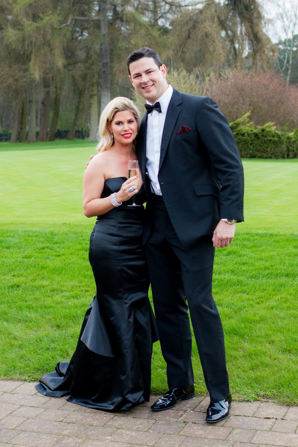 A couple in black tie and evening gown pose with champagne outside a birthday party - Event Photography