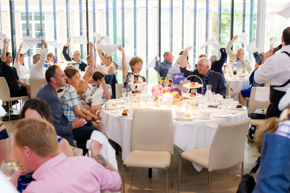 Guests sitting at a table wave napkins over their heads at a birthday tea at The Grove - Event Photography