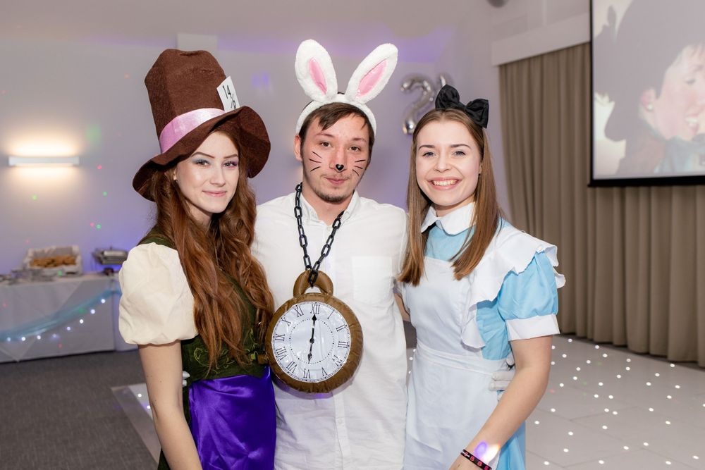 Group of friends in Alice in Wonderland costumes pose for the camera at a party - Event Photography