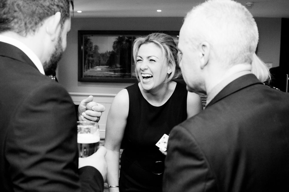 Woman laughs in a crowd of people at a black tie party - Event Photography