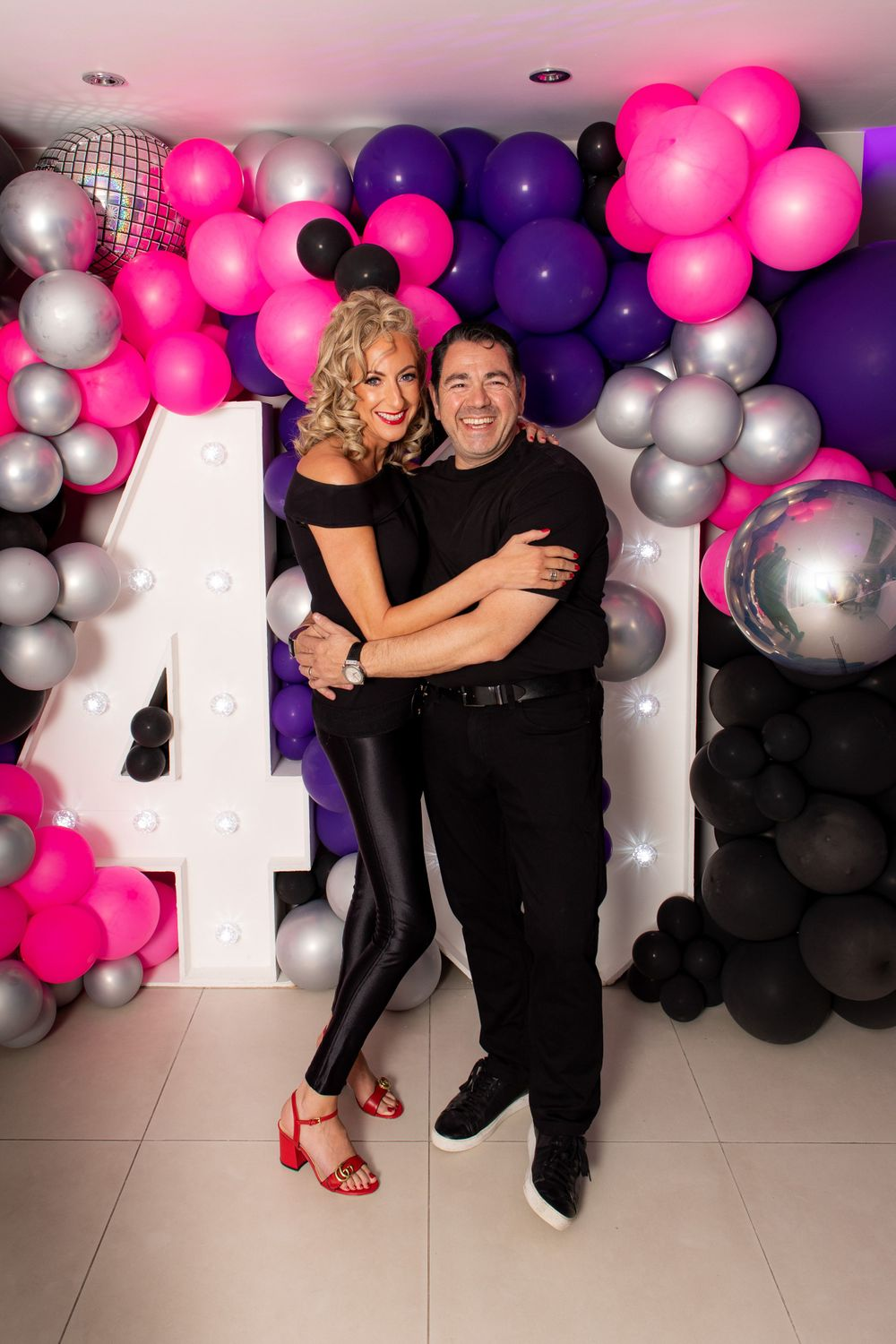 Couple pose on front of a balloon wall in costume as Danny and Sandy from Grease - Event Photography