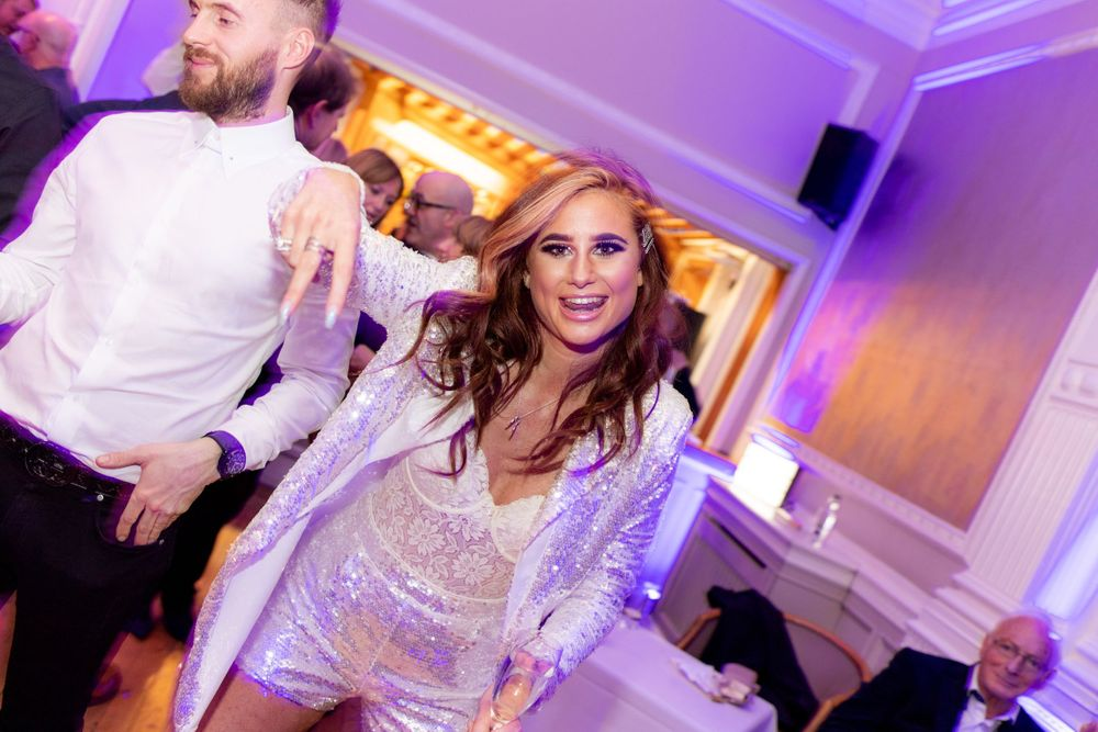 A young woman poses for the camera on the dance floor at a party - Event Photography