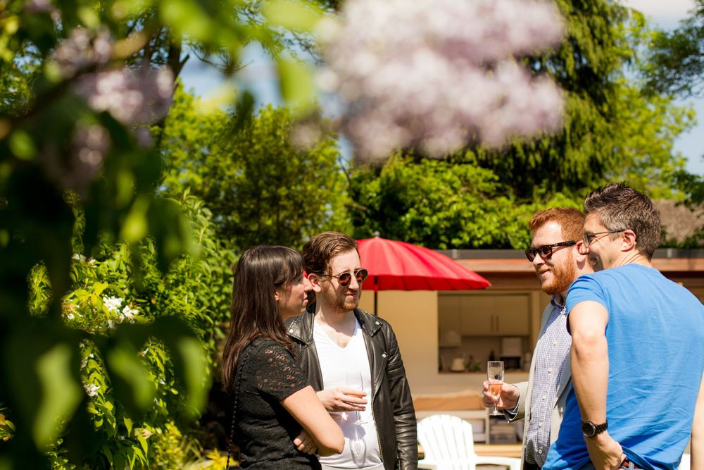 A crowd wearing sunglasses chats at a garden party  - Event Photography