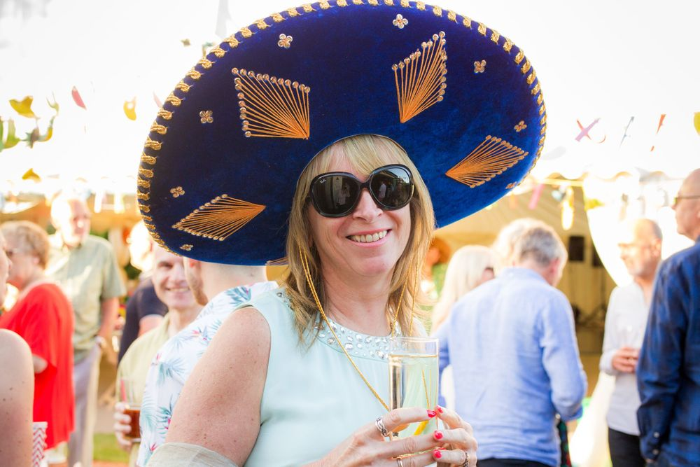 Woman in a sombrero and sunglasses poses fo the camera at a 50th birthday party - Event Photography