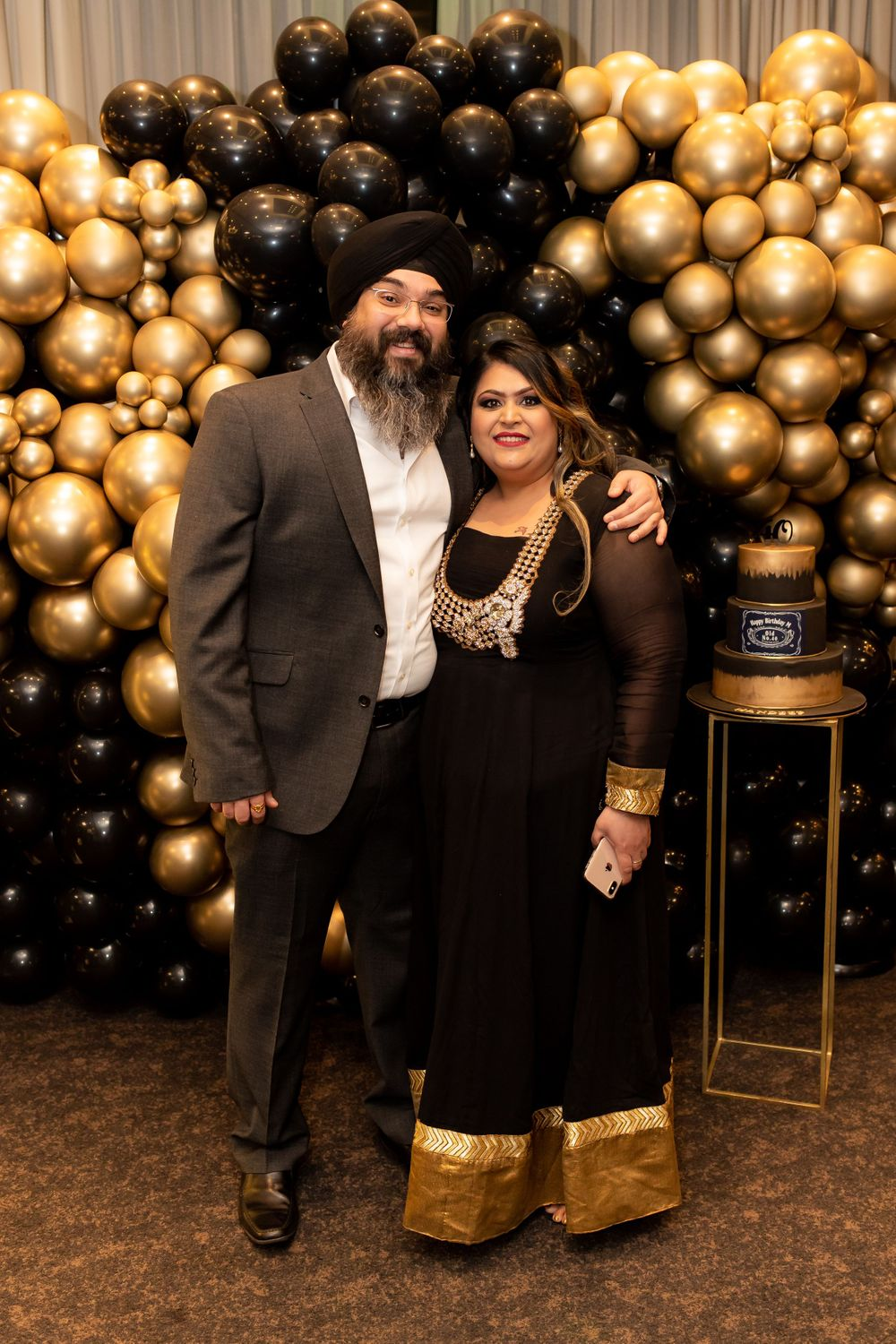 A Sikh couple wearing a black and gold sari stand in front of a balloon wall at 40th birthday party - Event Photography
