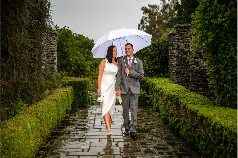Bride and groom on terrace in rain at Cragwood Hotel