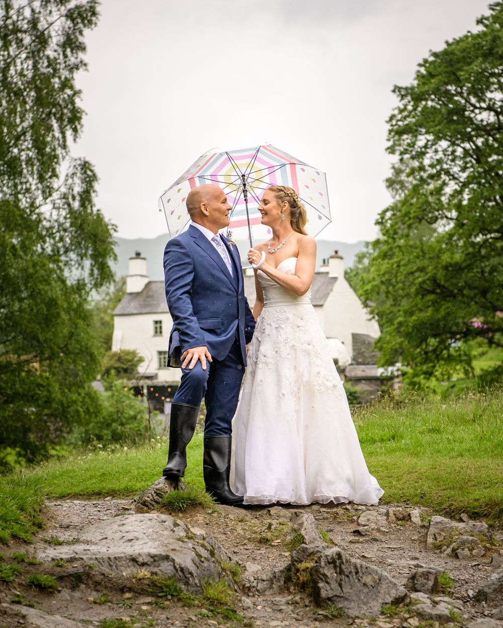 Bride and groom under umbrella at Cote How near Rydal Water