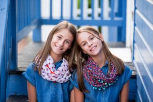 Twin Tween Sisters sitting on bright blue steps wearing coordinating scarfs and jean dresses.