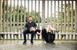 Tattooed couple pose for a engagement photo session with bride laying on grooms lap in black dress with leg exposed