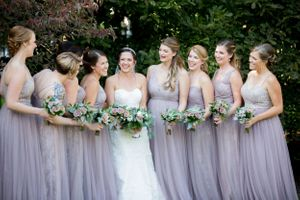 Bridesmaids in coordinateing lavender dresses chat with bride before the ceremony at Historic Waverly Mansion in MD