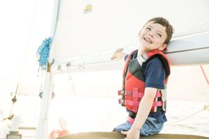 Young boy sits on the boom of a sailboat with large grin on his face while having a family photo session in Annapolis MD