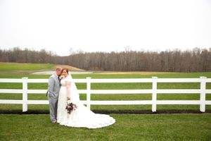 Redheaded bride and groom in front of white fence and bright green pasture just after saying I do in Maryland by DANIE