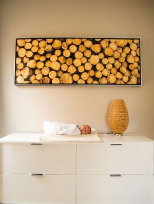 Modern Bright Yellow Art of Cut wood hanging on a wall with brand new baby on white MidCentury dresser during photo sesh