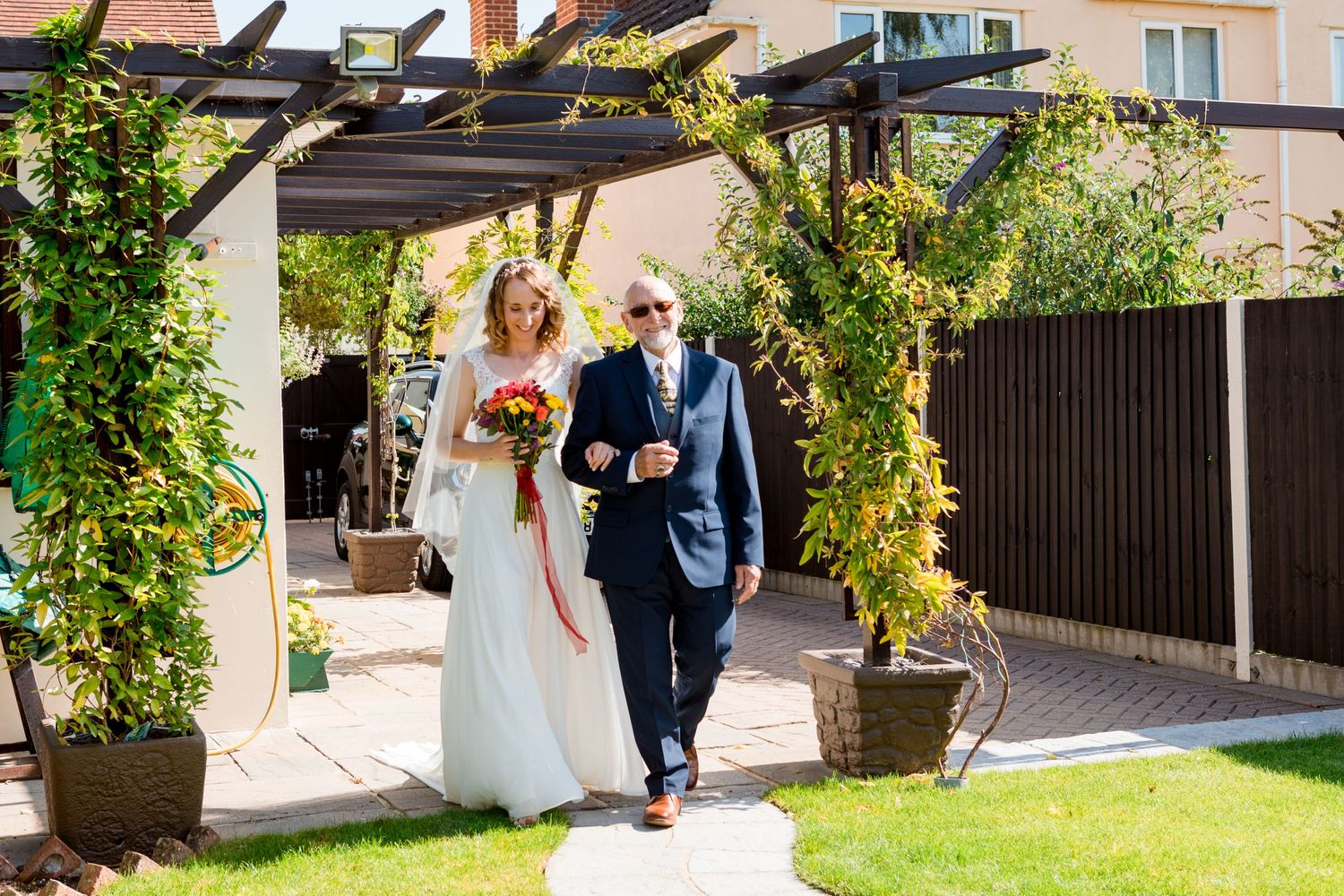 Small Garden Wedding Bride being walk down garden path by father