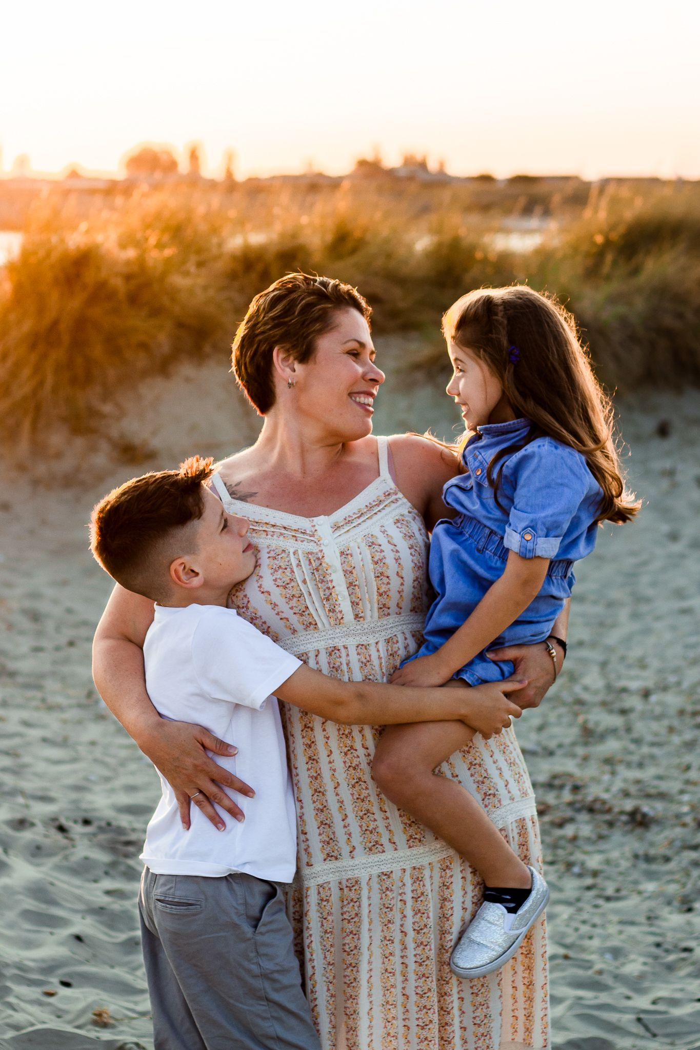 On a beach on Hayling Island a Mum smiles lovingly at her Son and Daughter while the Sun sets behind them.
