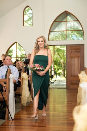 Bridesmaid walking down the aisle smiling at The Chapel at Gold Creek wedding in Canberra