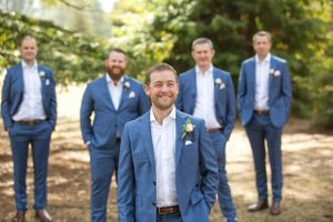 Groomsmen standing behind groom wearing navy suits at Redwood Forest Pialligo in Canberra