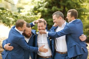 Groom with groomsmen in navy suits hugging before wedding ceremony at Redwood Forest Pialligo in Canberra