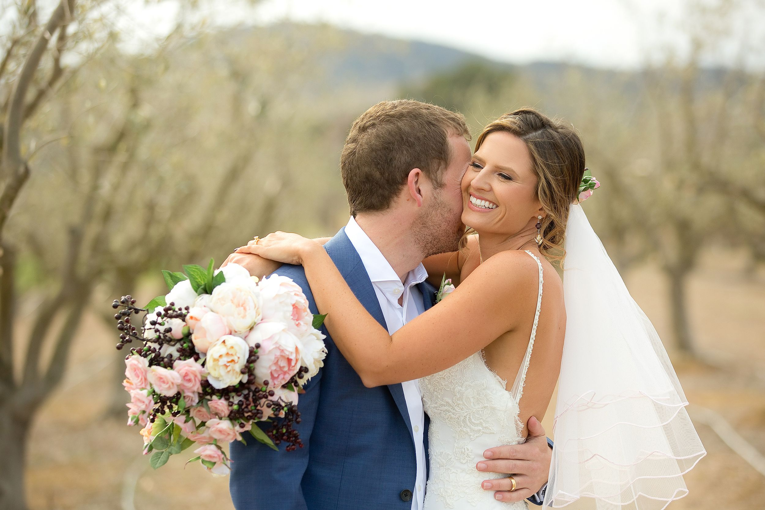 Groom kissing bride on the cheek in the olive grove at Pialligo Estate wedding in Canberra