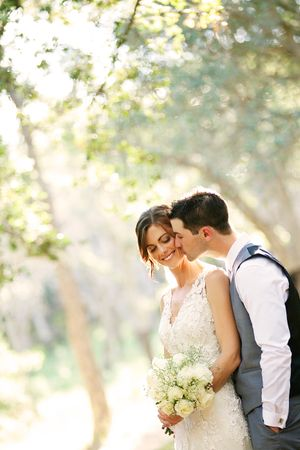 Groom kissing bride at the Cork Oak Forest at the National Arboretum of Canberra