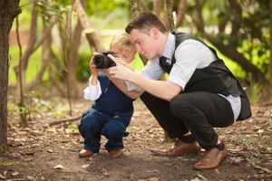 Teenage boy showing young boy how to take photos with a camera at a wedding at Noosa Main Bach in Queensland