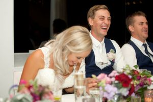 Bride and groom laughing at The Noosa Boathouse wedding reception during speeches in Queensland