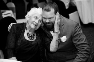 Grandma affectionately hugging wedding guest at Hotel Realm Barton in Canberra