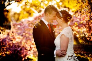 Bride and groom portraits in front of cherry blossom trees at Four Winds Winery in Canberra