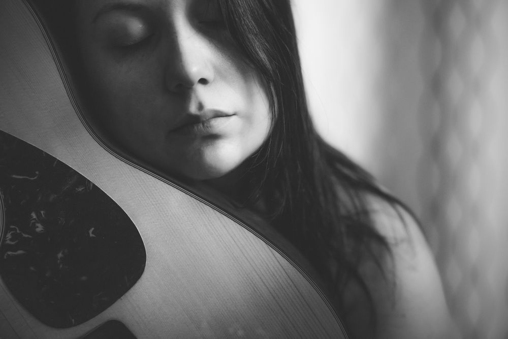 woman holding face against guitar with eyes closed lovingly, issaquah wa by shutterbabe snapshots