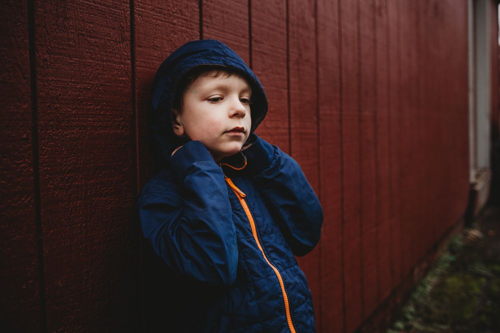 young boy leaning against red wall at ravensdale market, issaquah wa by shutterbabe snapshots