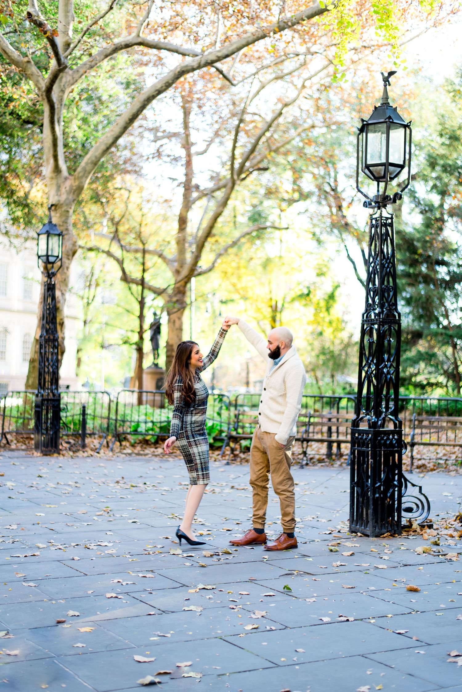 cute young couple spins around during engagement pictures at NYC City Hall in November