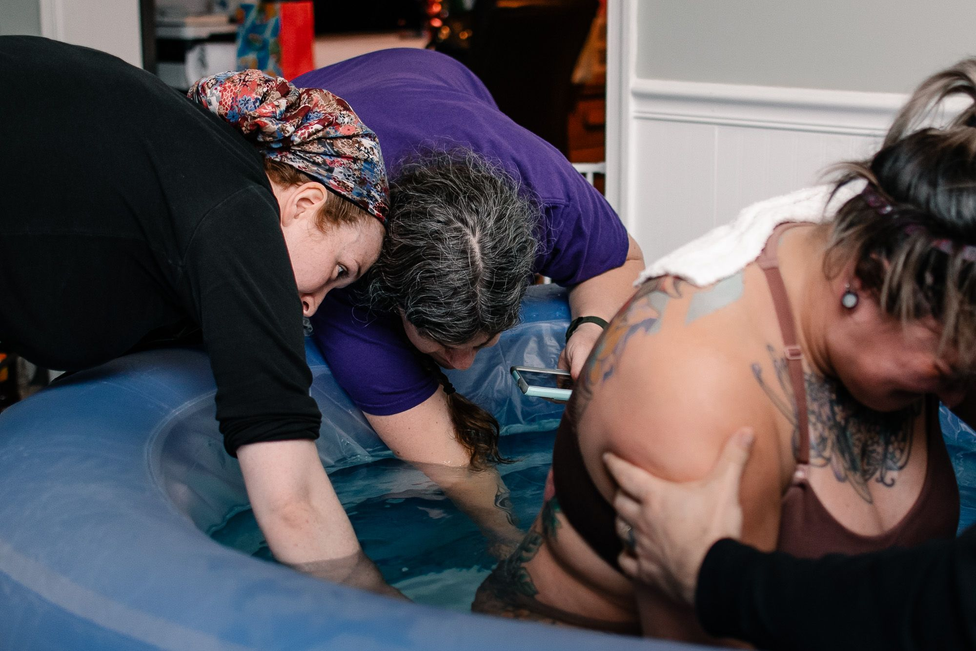 2 maryland midwives assisting woman in birthing pool during home birth