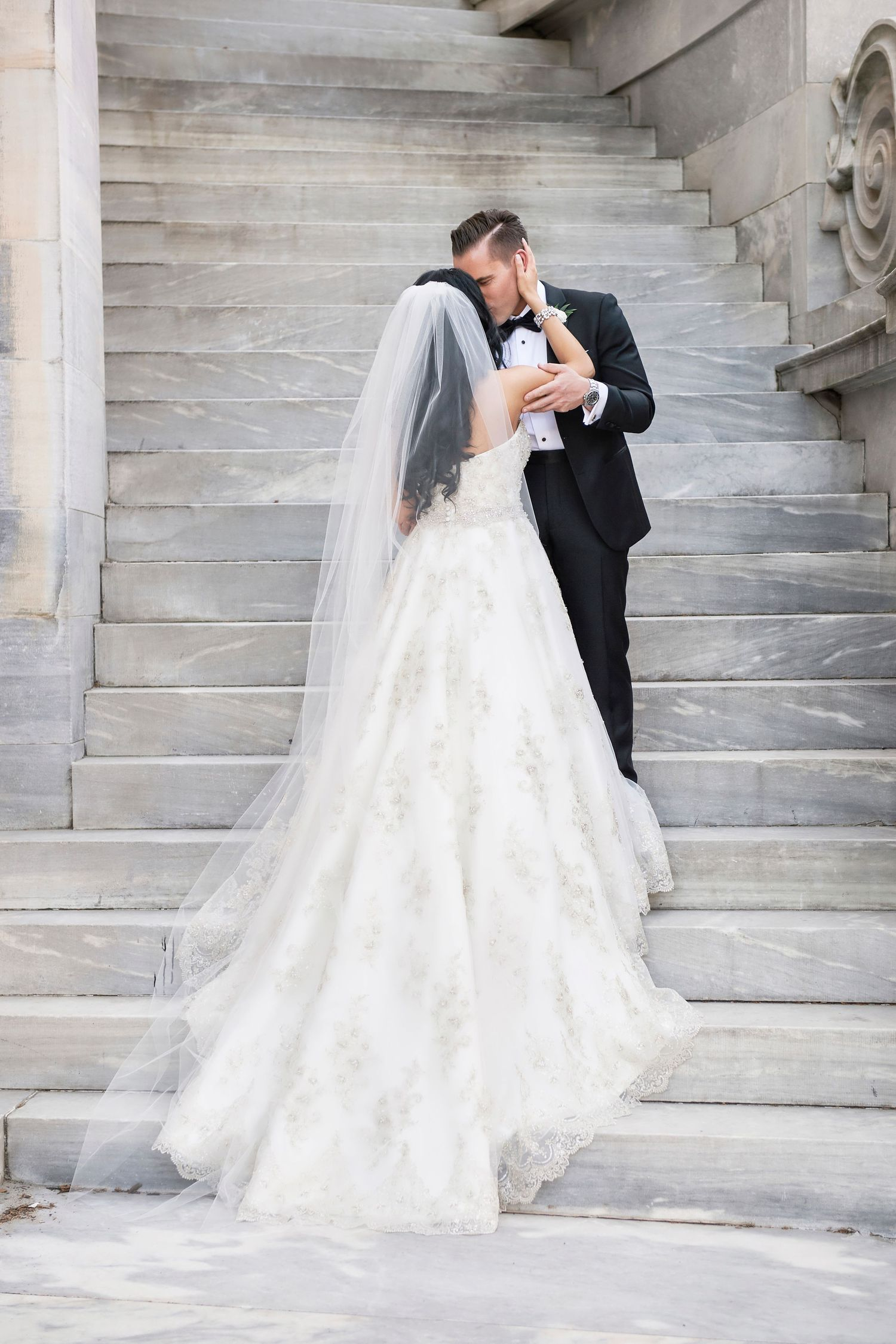 bride and groom on stairs at Merchant Exchange Building in old city philadelphia