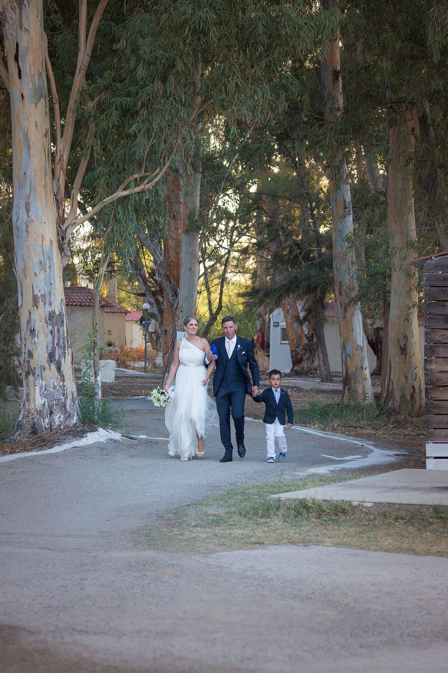 couple with their nephew walking towards the boat which will transfer them to the reception