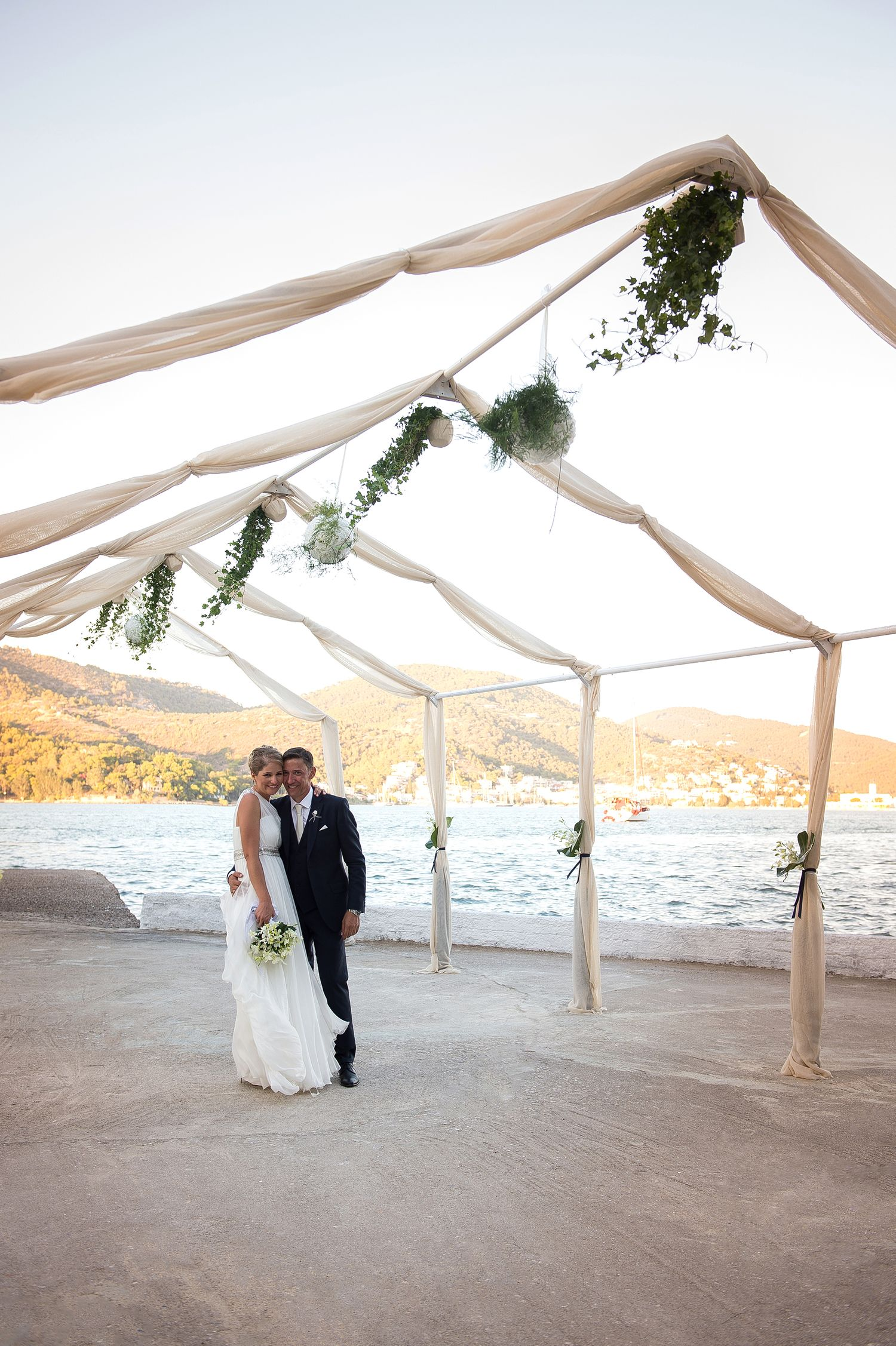 couple posing in front of the poros sea under a chapel decorated with green leaves