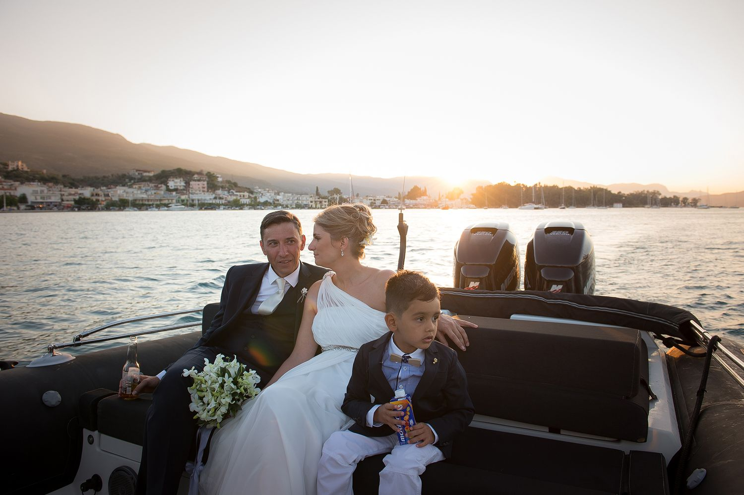 couple with their nephew on the boat to the reception with poros island in the background