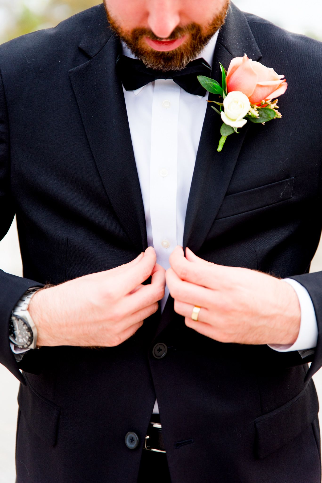groom with beard buttoning his black suit, showing coral rose boutonniere