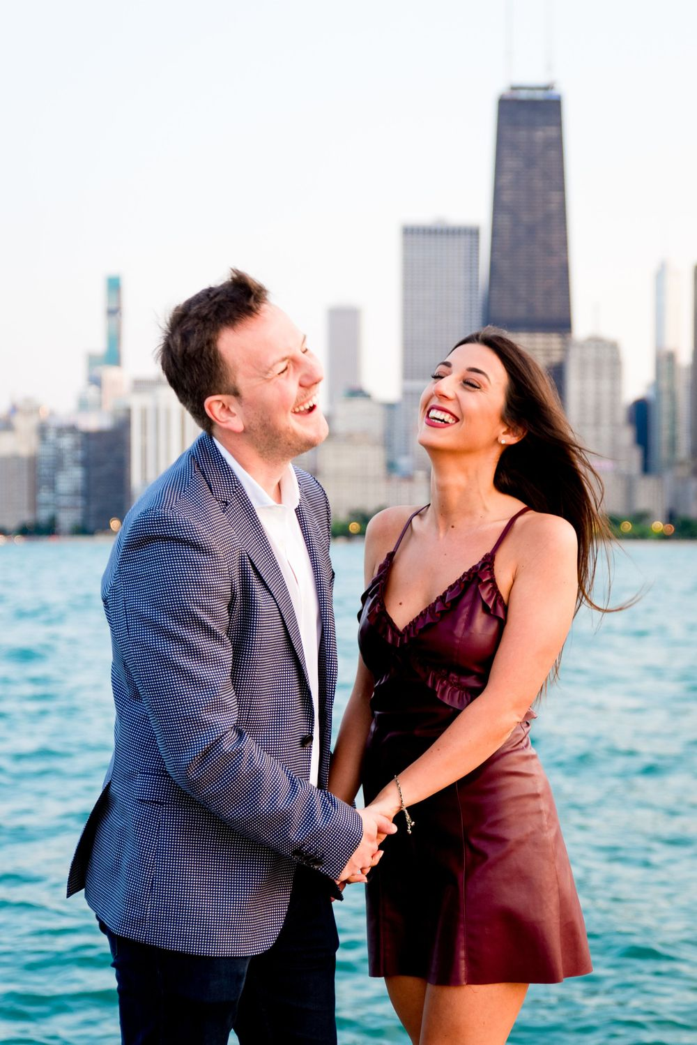 man and woman in formalwear holding hands laughing in front of Chicago skyline after man proposed at North Ave Beach
