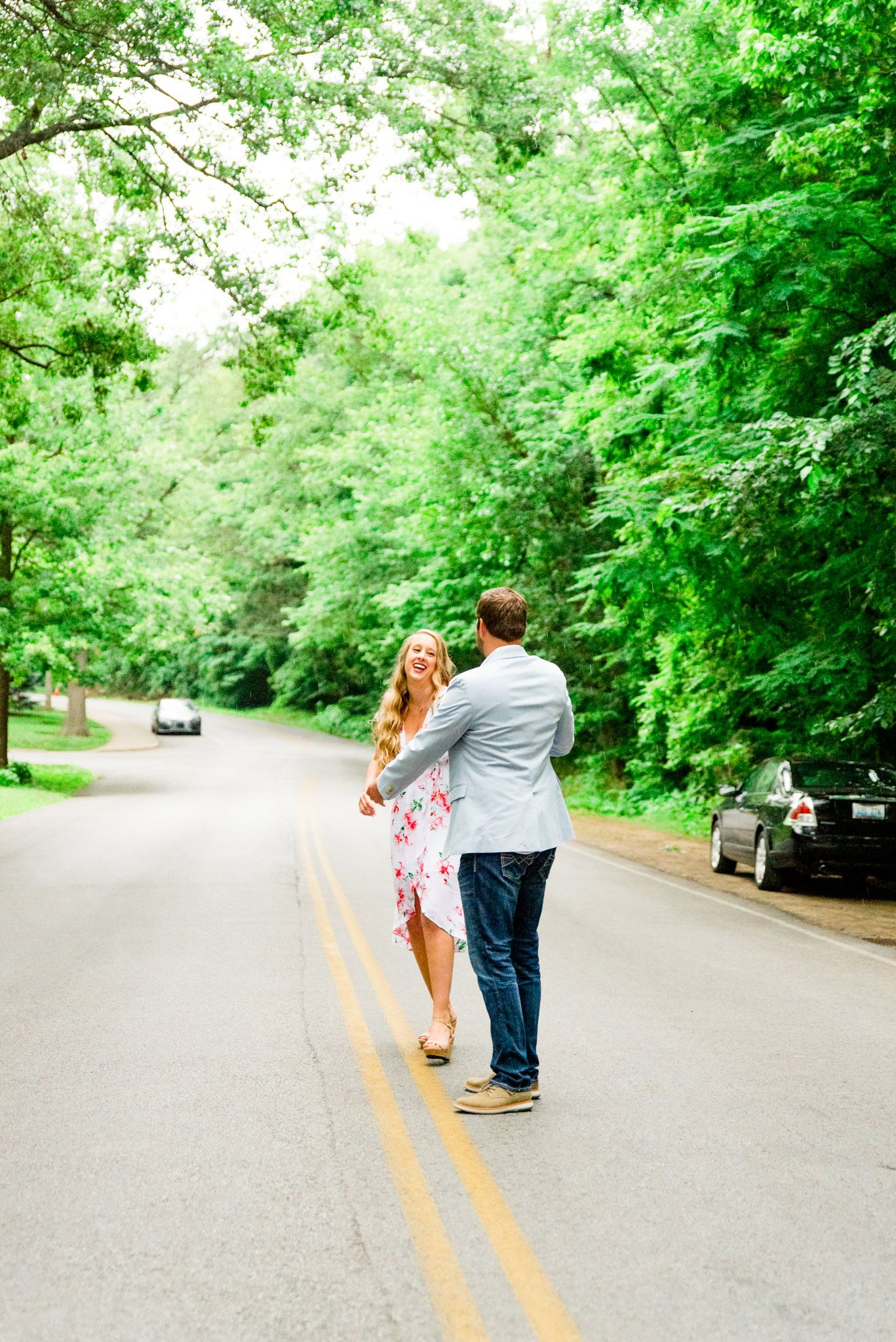 engaged couples in floral dress and light blue suit jacket and jeans dancing in middle of road under trees