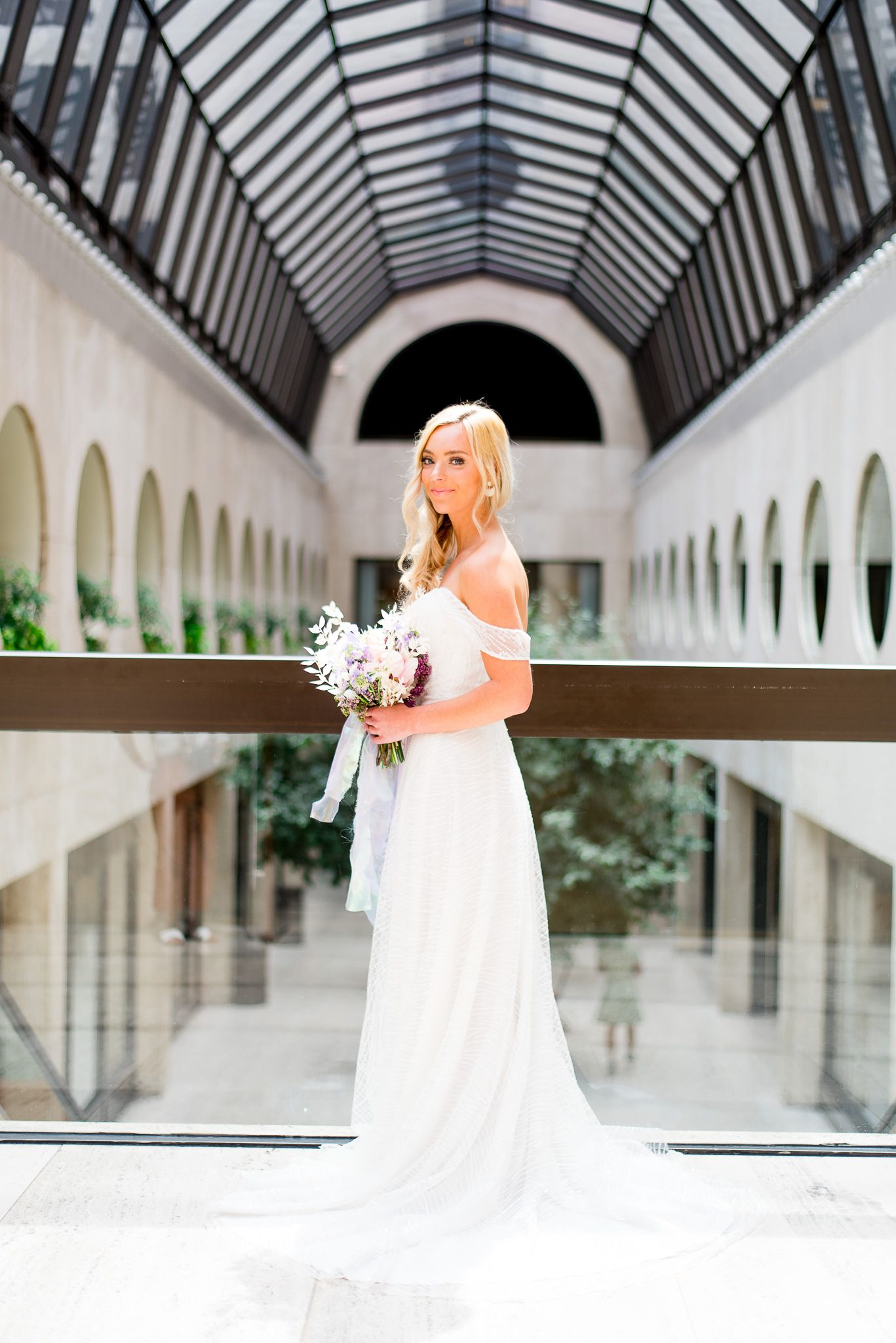 blonde bride smirking in atrium of The Center Cincinnati with pink and purple wedding flowers