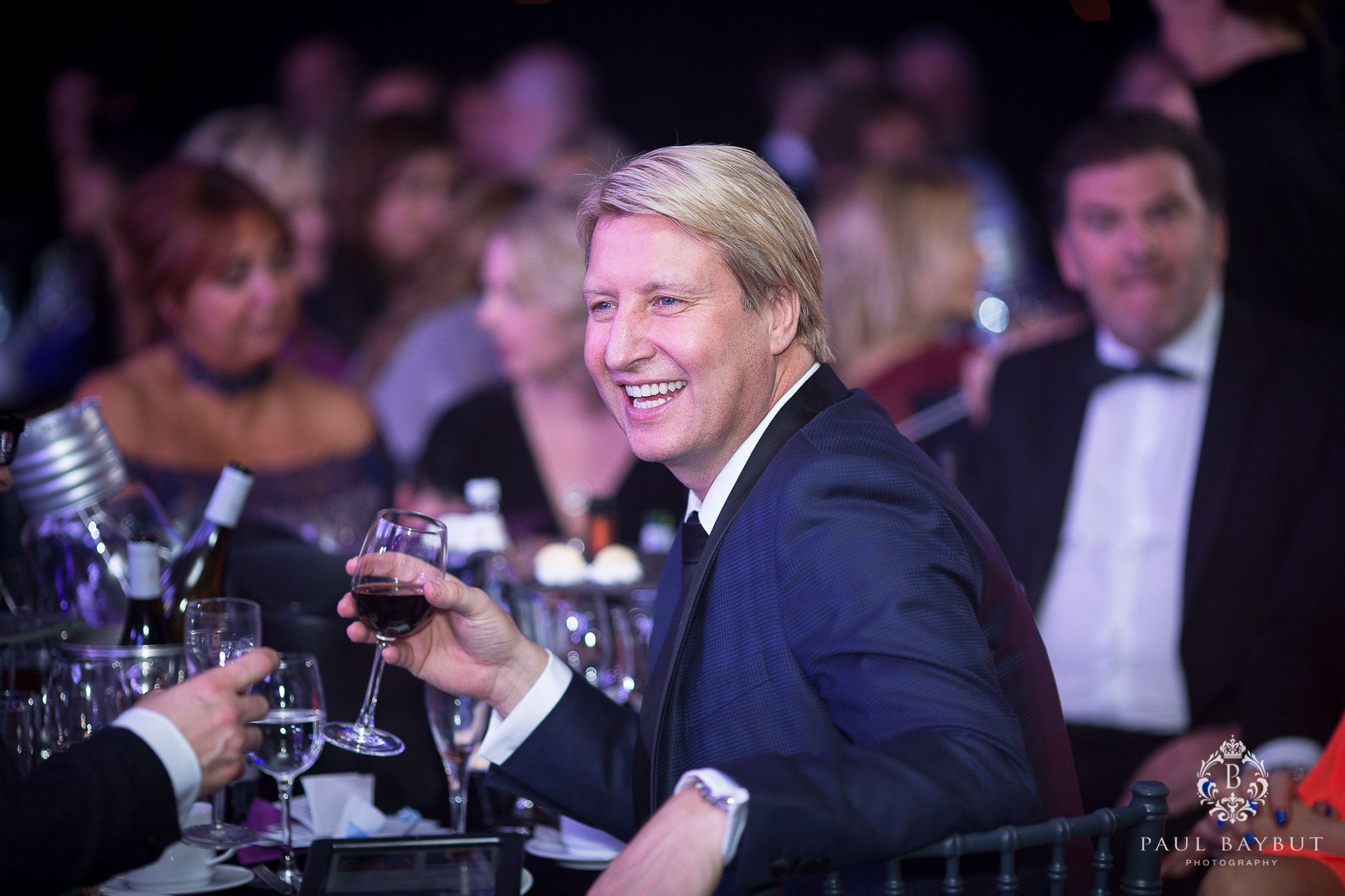 Smiling male guest sat a a table and holding a glass of wine during a charity ball event in Manchester