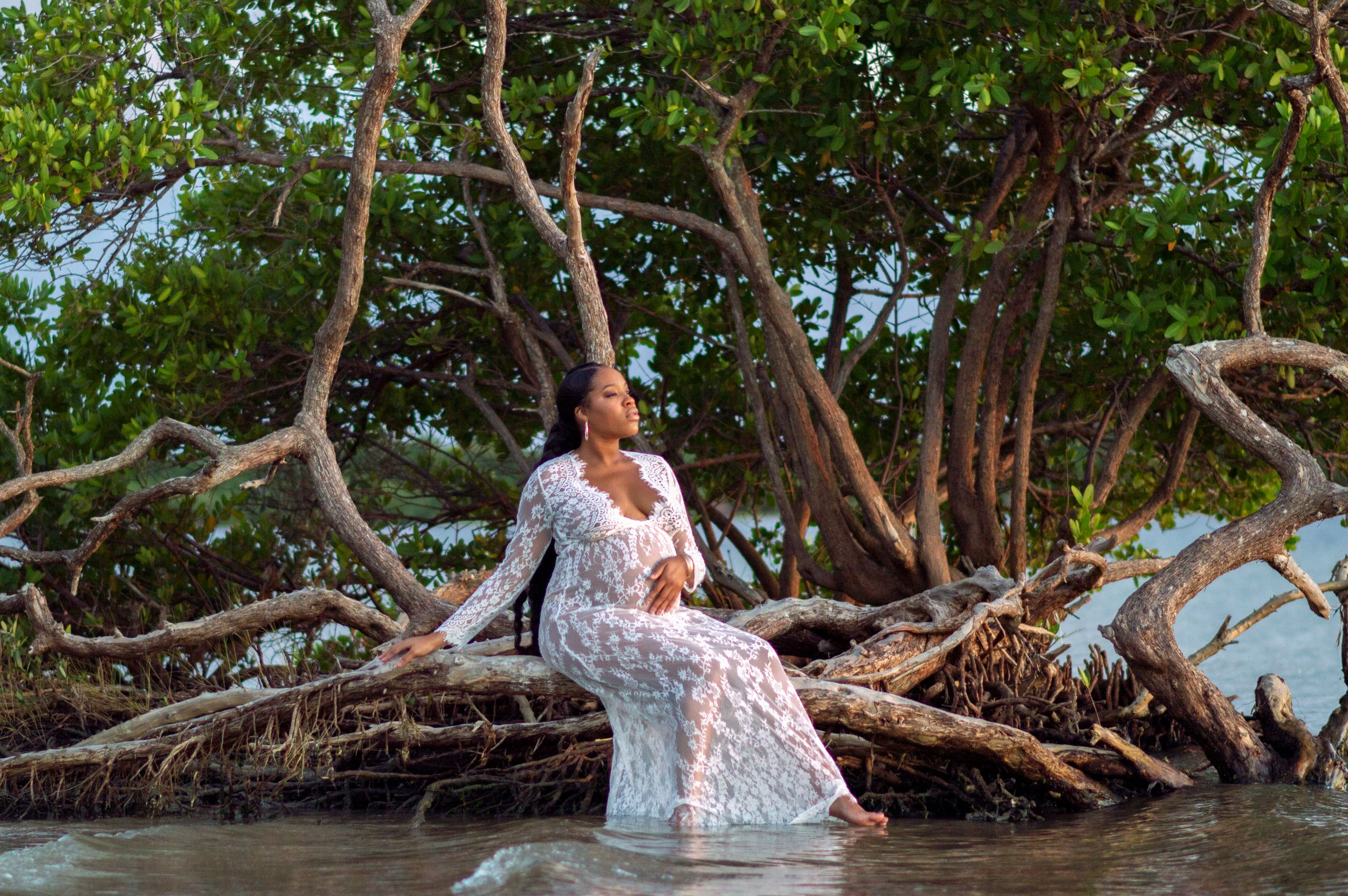 Pregnant mother sitting on a tree in the water