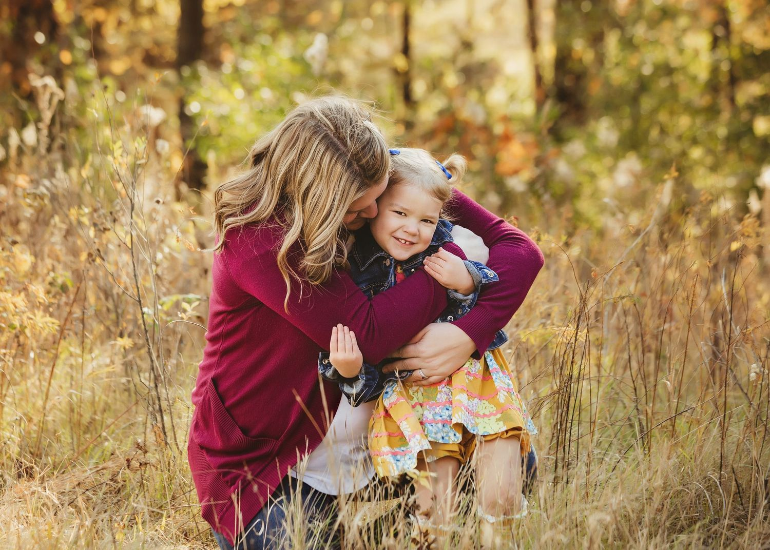 mom hugging daughter in field