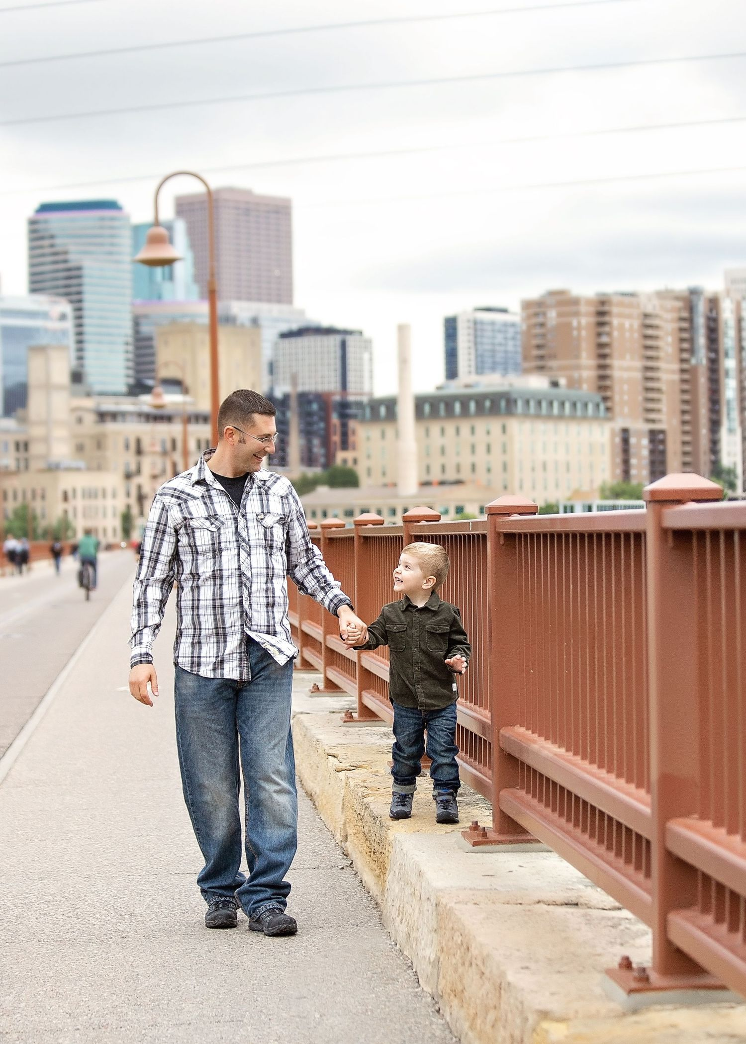 dad walking with son stone arch bridge minneapolis